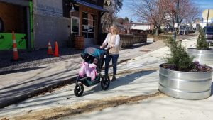 Mom pushing stroller in multi-use path on Coxe Ave