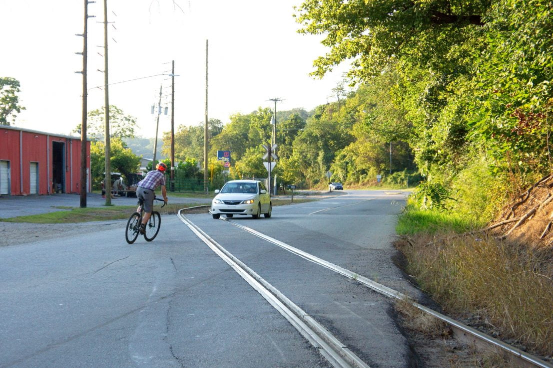 Asheville, Riverside Drive, northbound cyclist attempts to cross RR tracks by veering into oncoming traffic