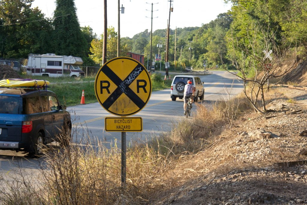Cyclist surrounded by cars approaching railroad crossing