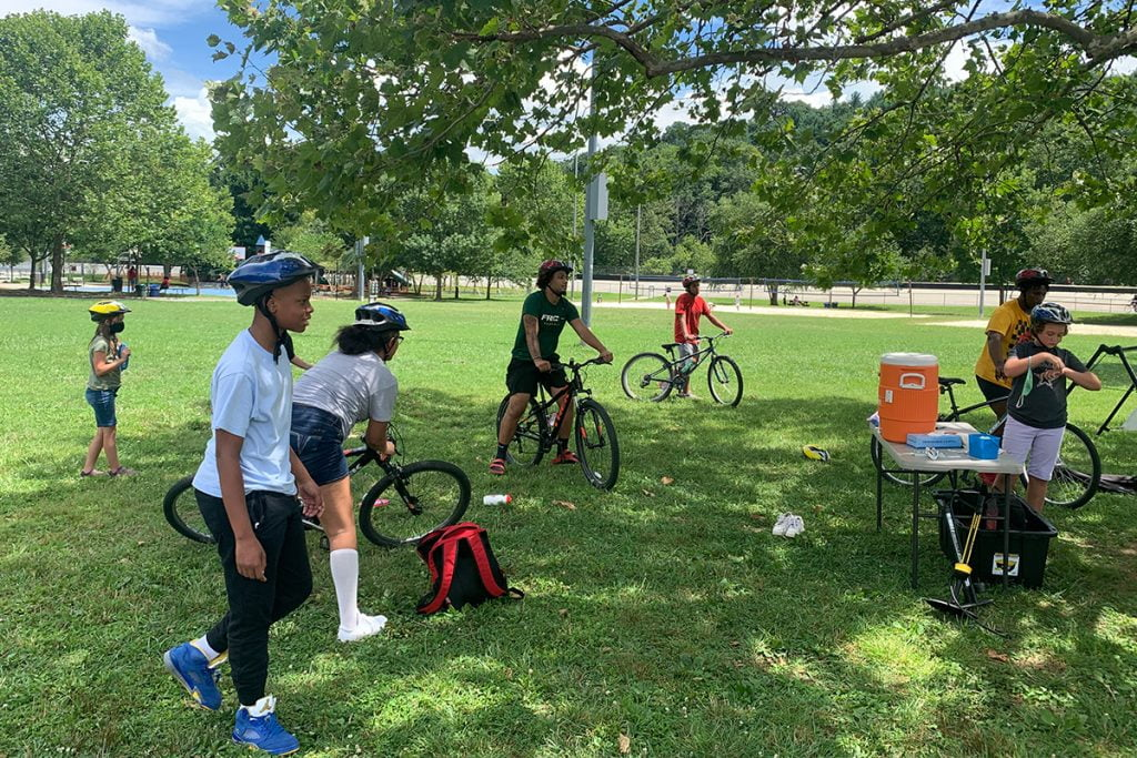 group of students on bikes congregate around a water cooler while social distancing in Asheville