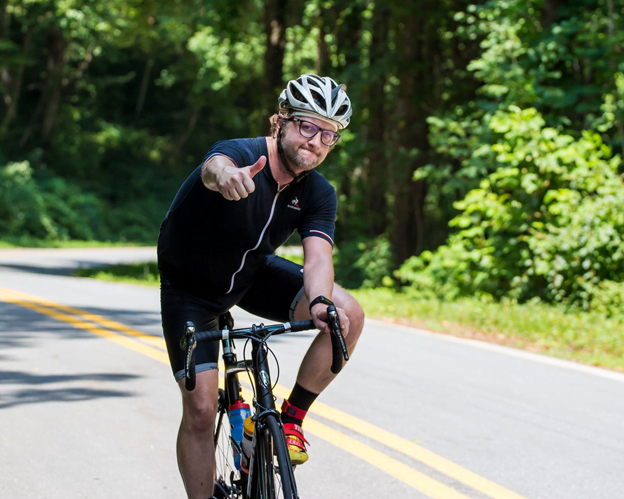 Asheville resident on bike gives a thumbs up while biking uphill on sunlit paved road