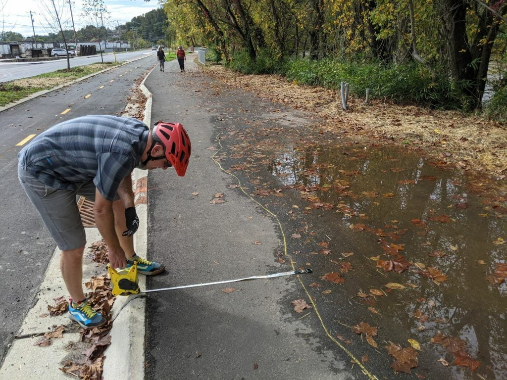 Large water puddle on greenway with Mike Sule measuring