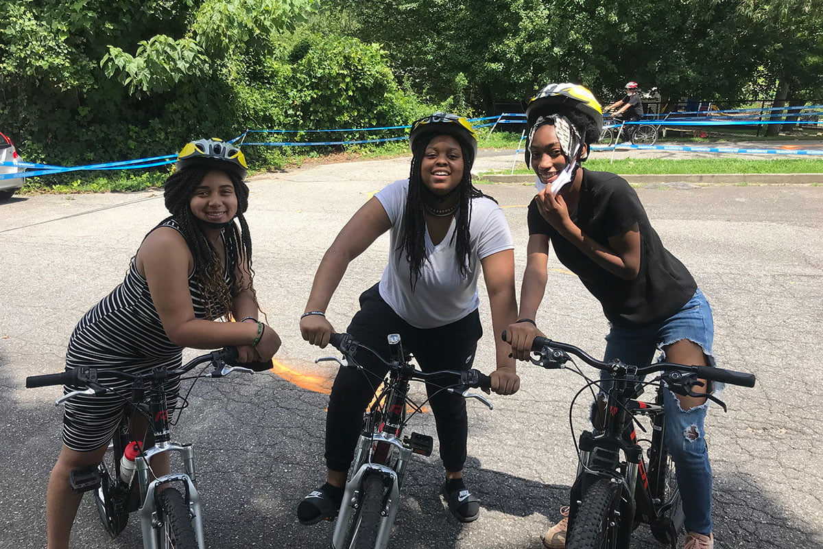 Three Girls Smiling on Bikes